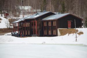 Vindelfjällens forskningsstation. Brunt hus med röda knutar i snö.