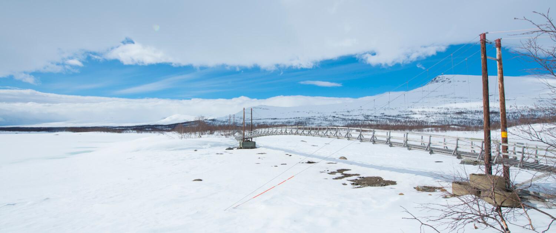 En hängbro över en frusen sjö med snö på. Tärnasjöbroarna.