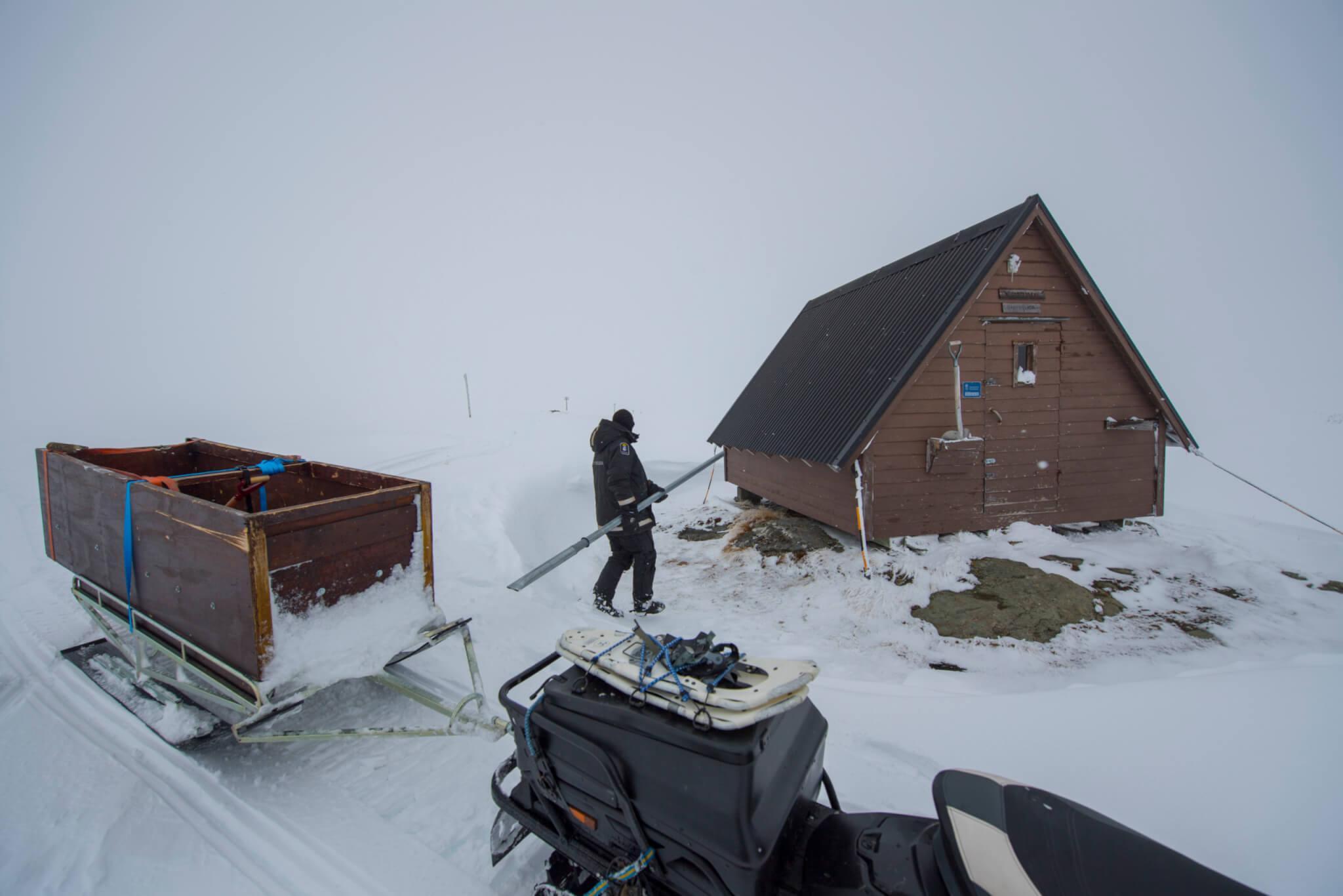 En person bär en planka till en brun liten stuga. Det är vinter och en skoter står parkerad i förgrunden.