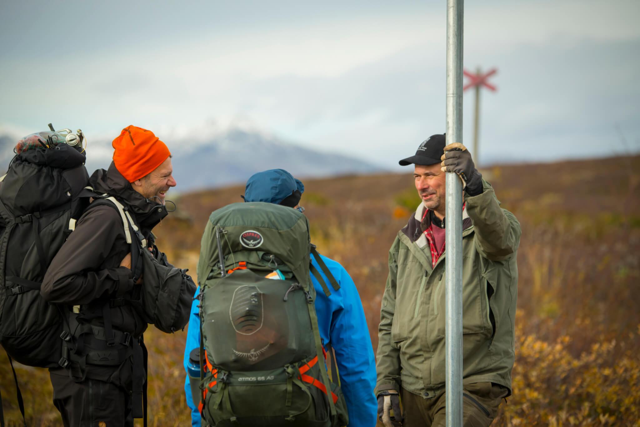 Två vandrare som står vid ett ledkryss och pratar med en naturbevakare. Naturbevakaren ler mot vandrarna.