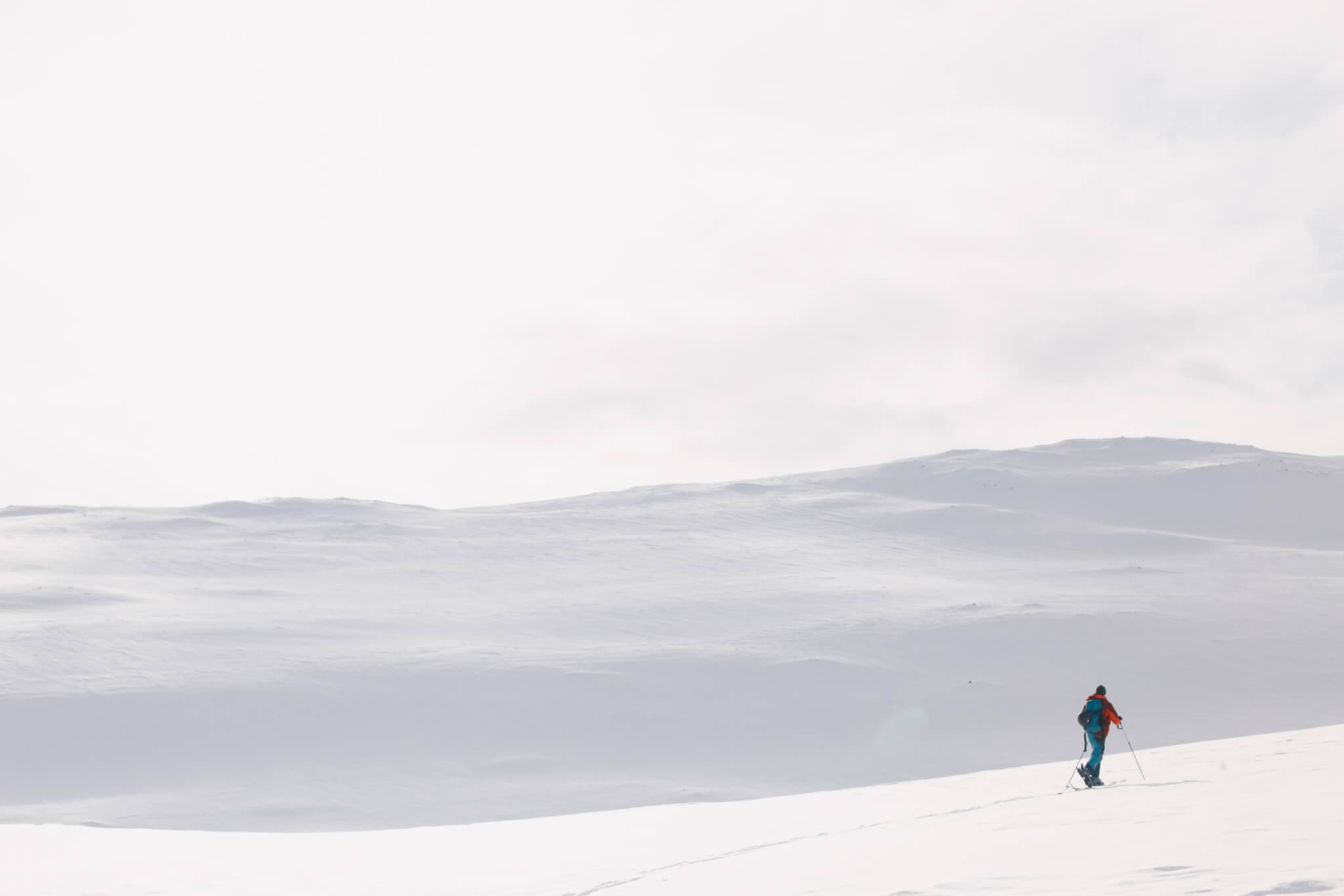 Skidåkare går på tur i snöigt fjällandskap.