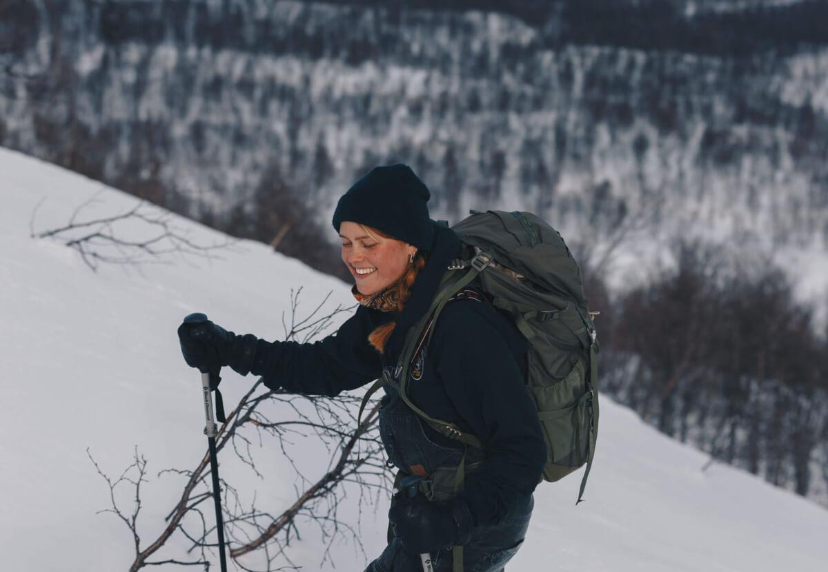Kvinna går på skidor upp för bergsluttning.