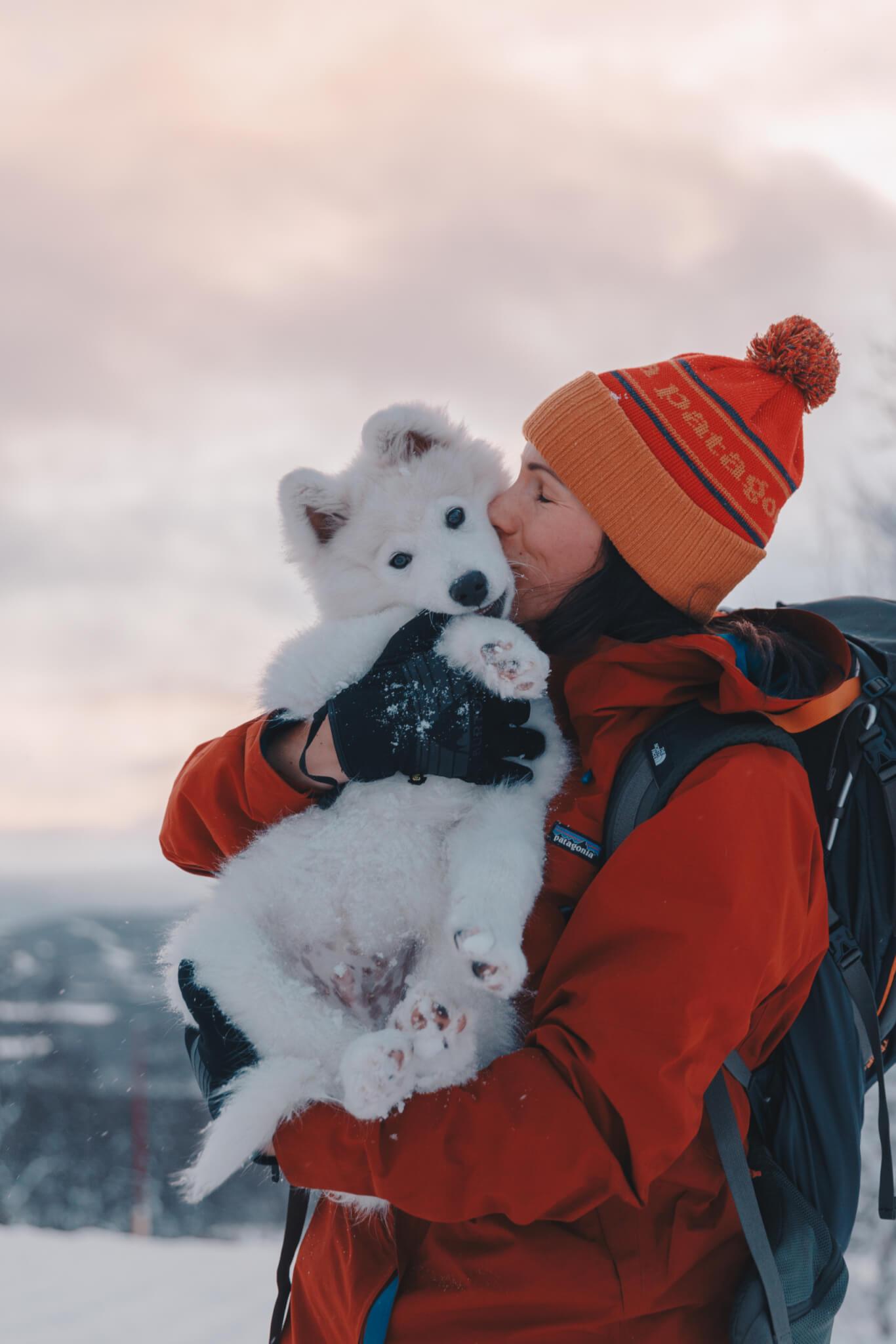 Kvinna håller i vit hundvalp och pussar den på kinden.
