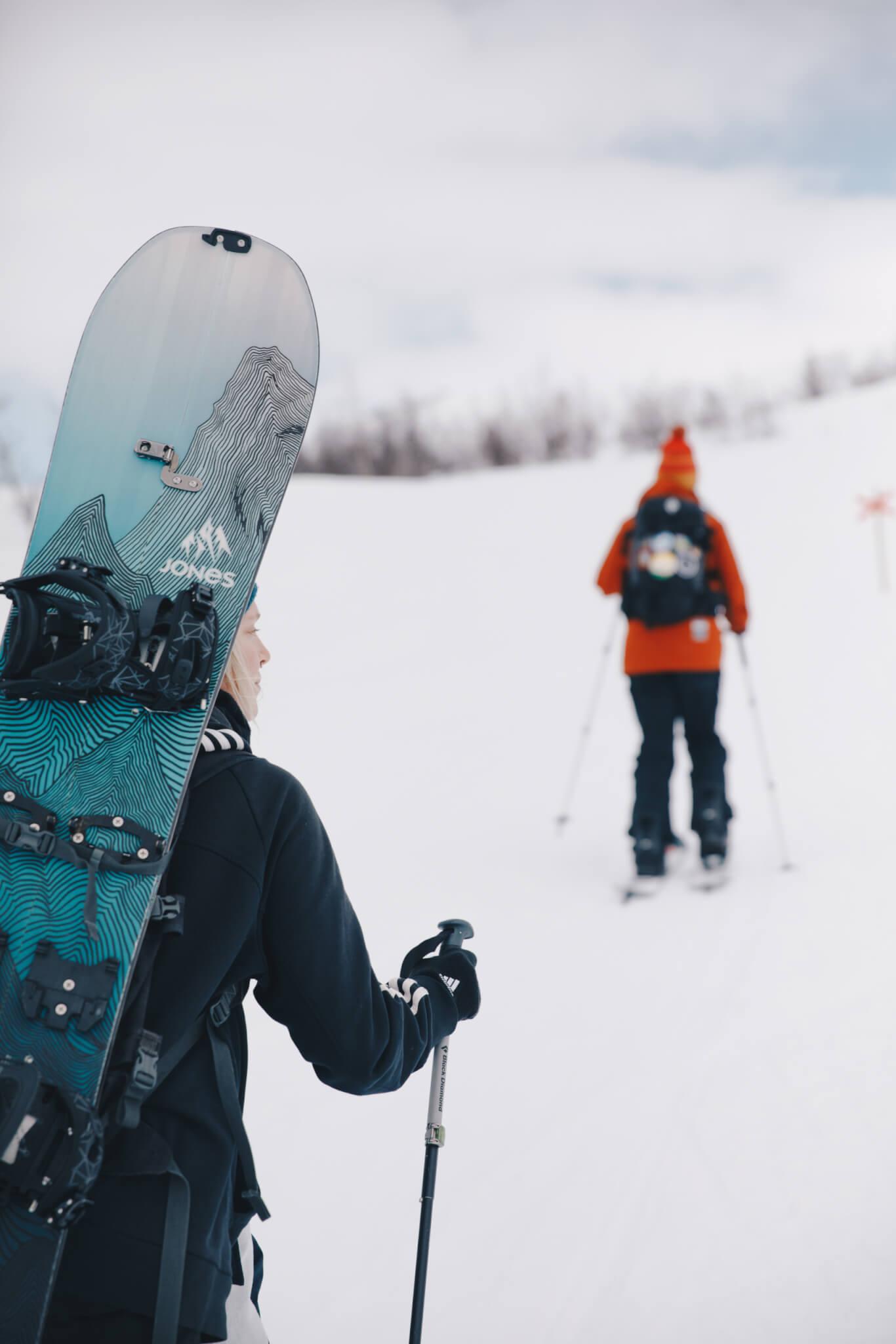 Person med snowboard på ryggen går upp för snöig backe.