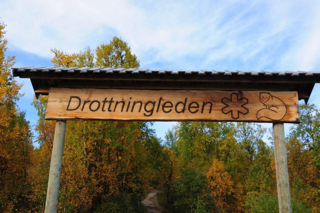 """Skylt i trä med texten """"Drottningleden""""."""