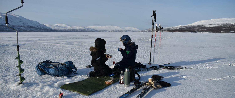 Två barn sitter på en sjöis mellan isborr och längsskidor. De håller i pimpelspön.