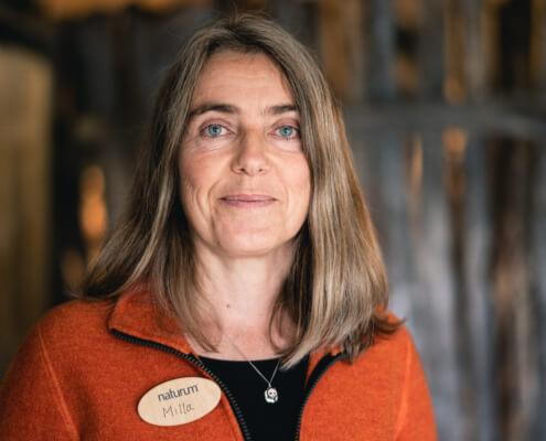 Porträtt av Ludmilla Wieslander. Kvinna i röd fleece tittar leende in i kameran.