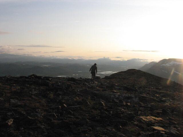 En person med hatt vandrar på en stenig fjällkam.