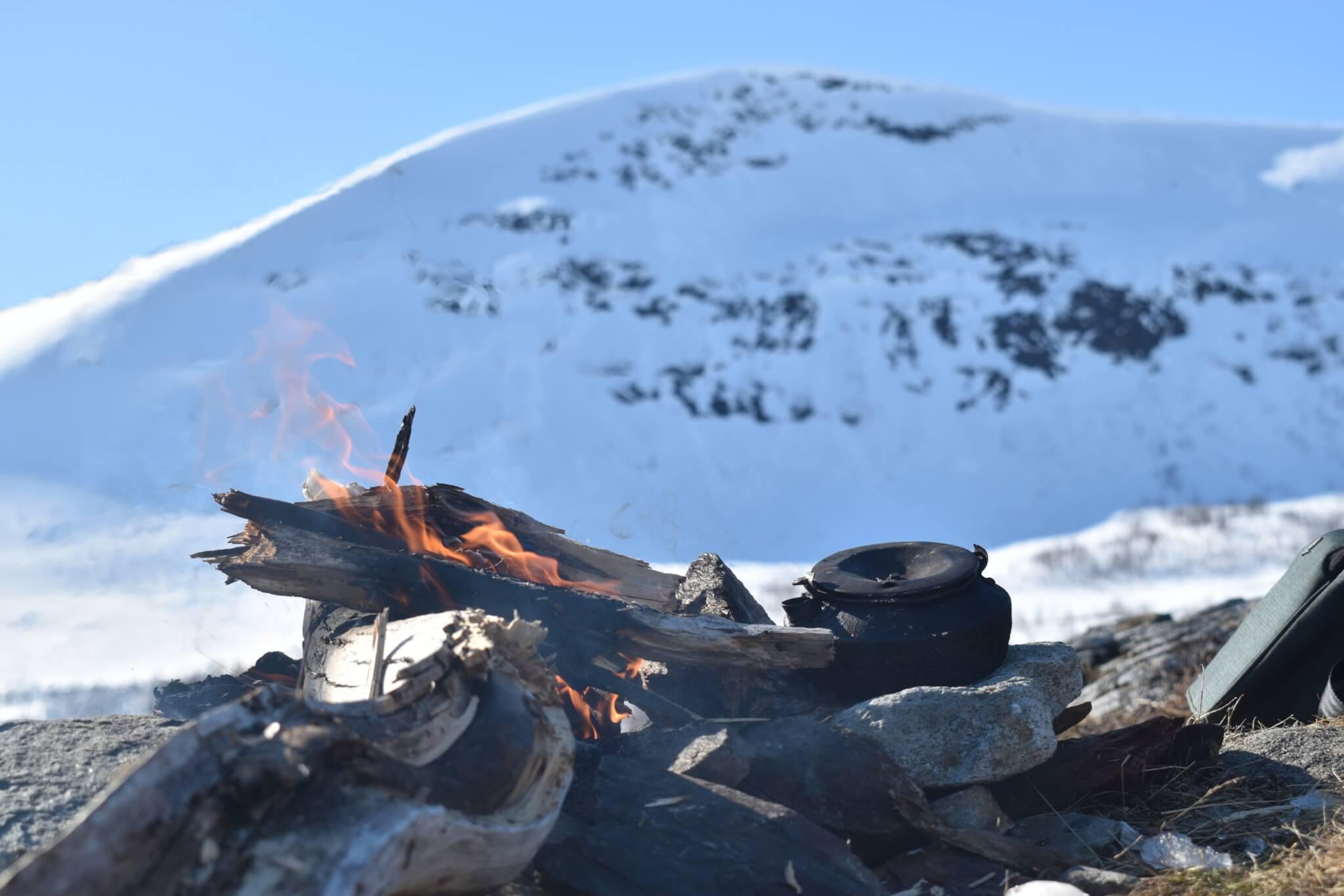 En öppen eld på kalfjäll med sotig kaffepanna bredvid. I bakgrunden stort snötäckt fjäll.
