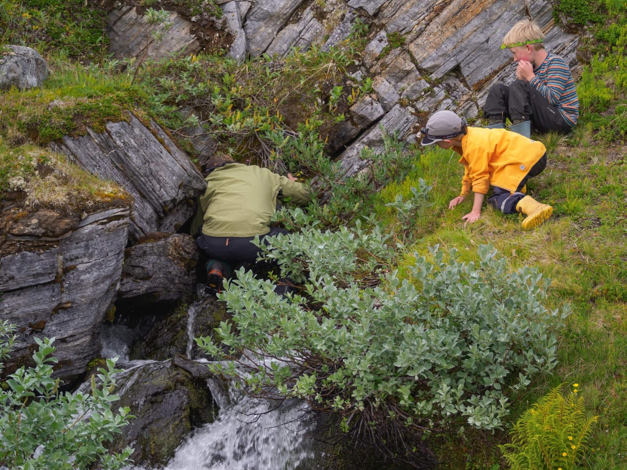 En vuxen person med grön tröja står med ryggen vänd mot kameran och tittar in i en bergskreva. Ett barn står på sidan och tittar på den vuxne.