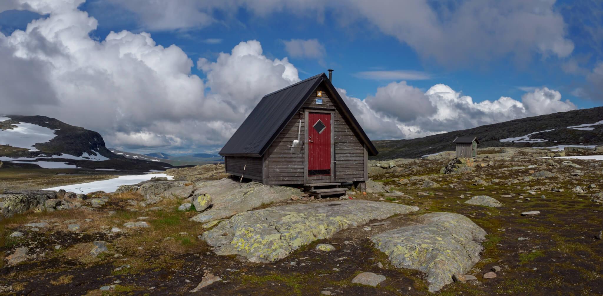Vallentjåkke/Marinstugan. En grå liten stuga med röd dörr uppe på kalfjäll med blå himmel och moln i bakgrunden.