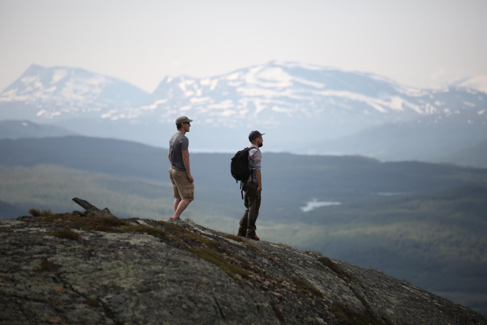 Två män står på ett fjäll och blickar till höger .