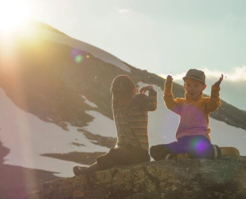 Två barn sitter på en sten och viftar bort myggor. Solen lyser in i kameran och bakom dem syns kalfjäll med snö på.