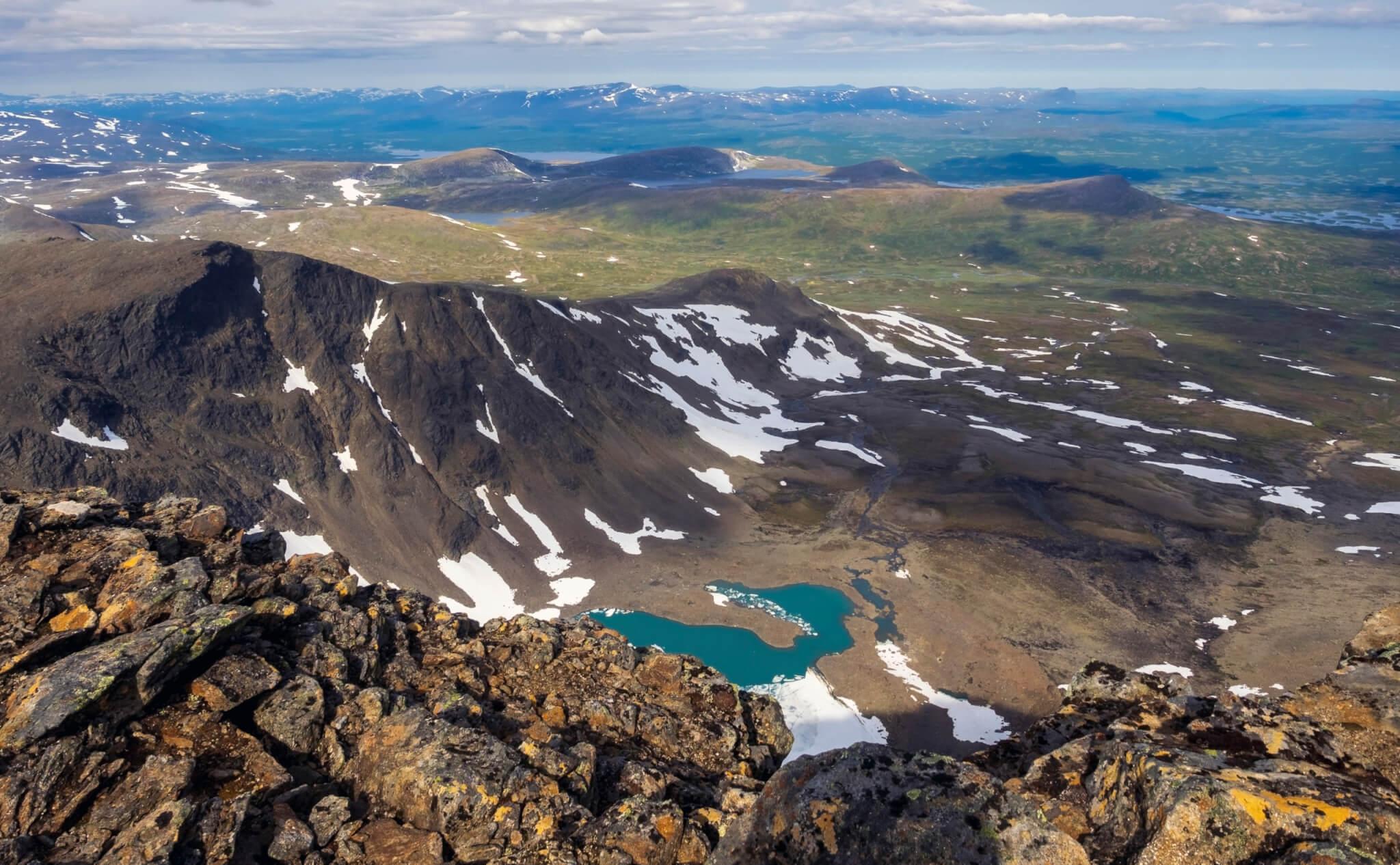 Norra Sytertoppen mot Ammarnäsfjällen sommardag. Stenskravel, grönt vatten och stor fjälldal.
