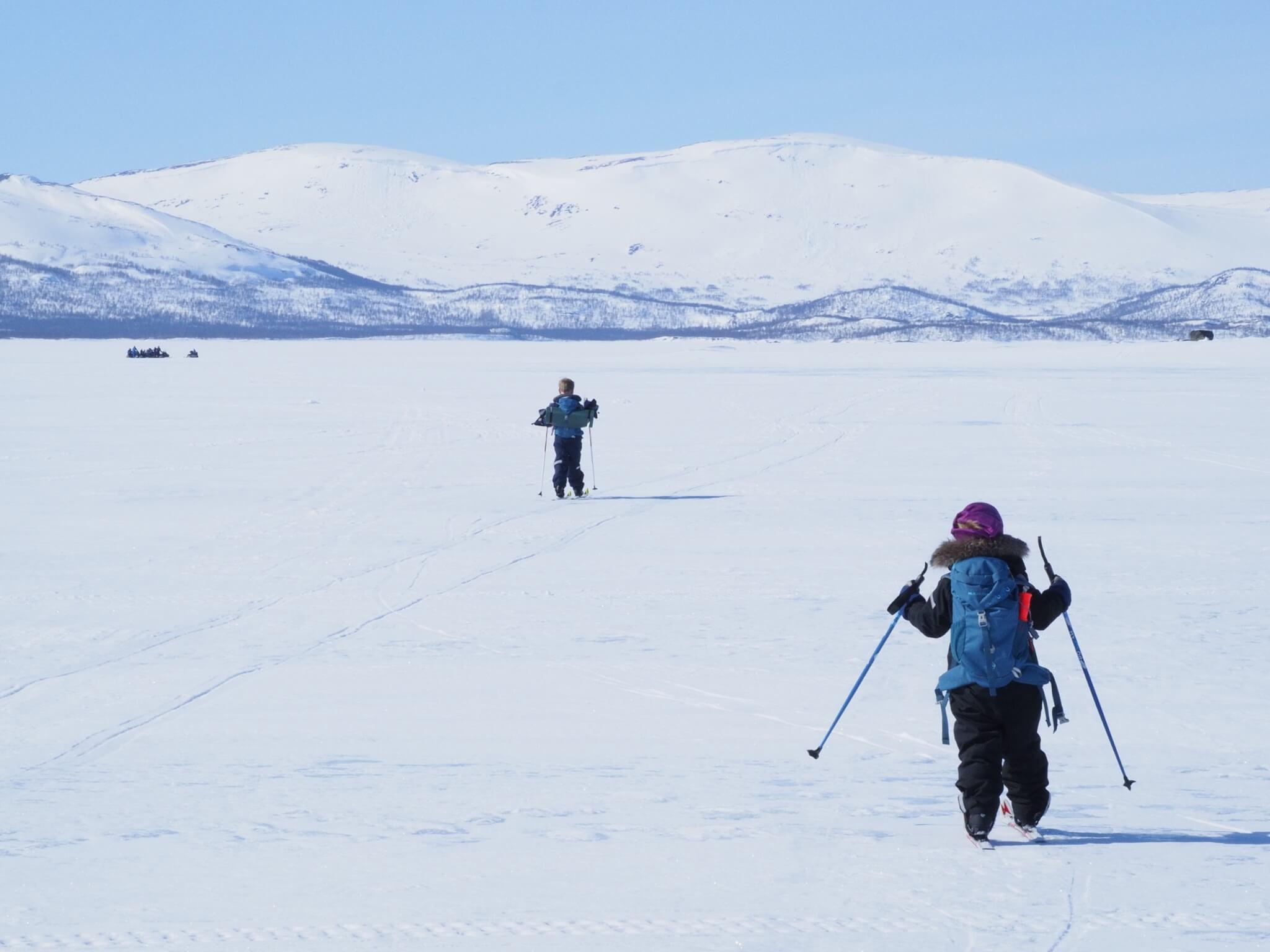 Vinterbild. Två barn åker längdskidor på en sjö.
