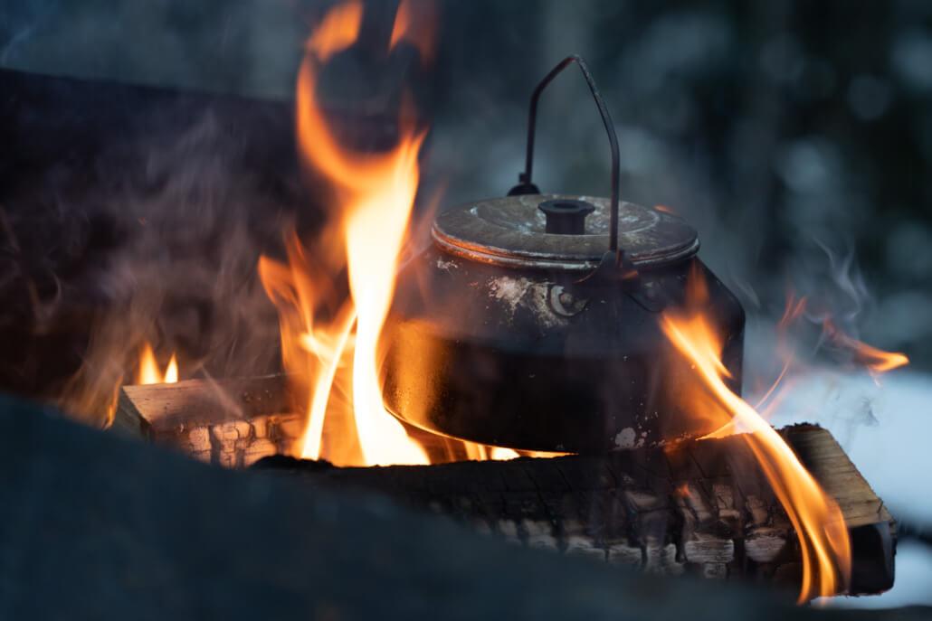 En sotig kaffepanna över öppen eld.