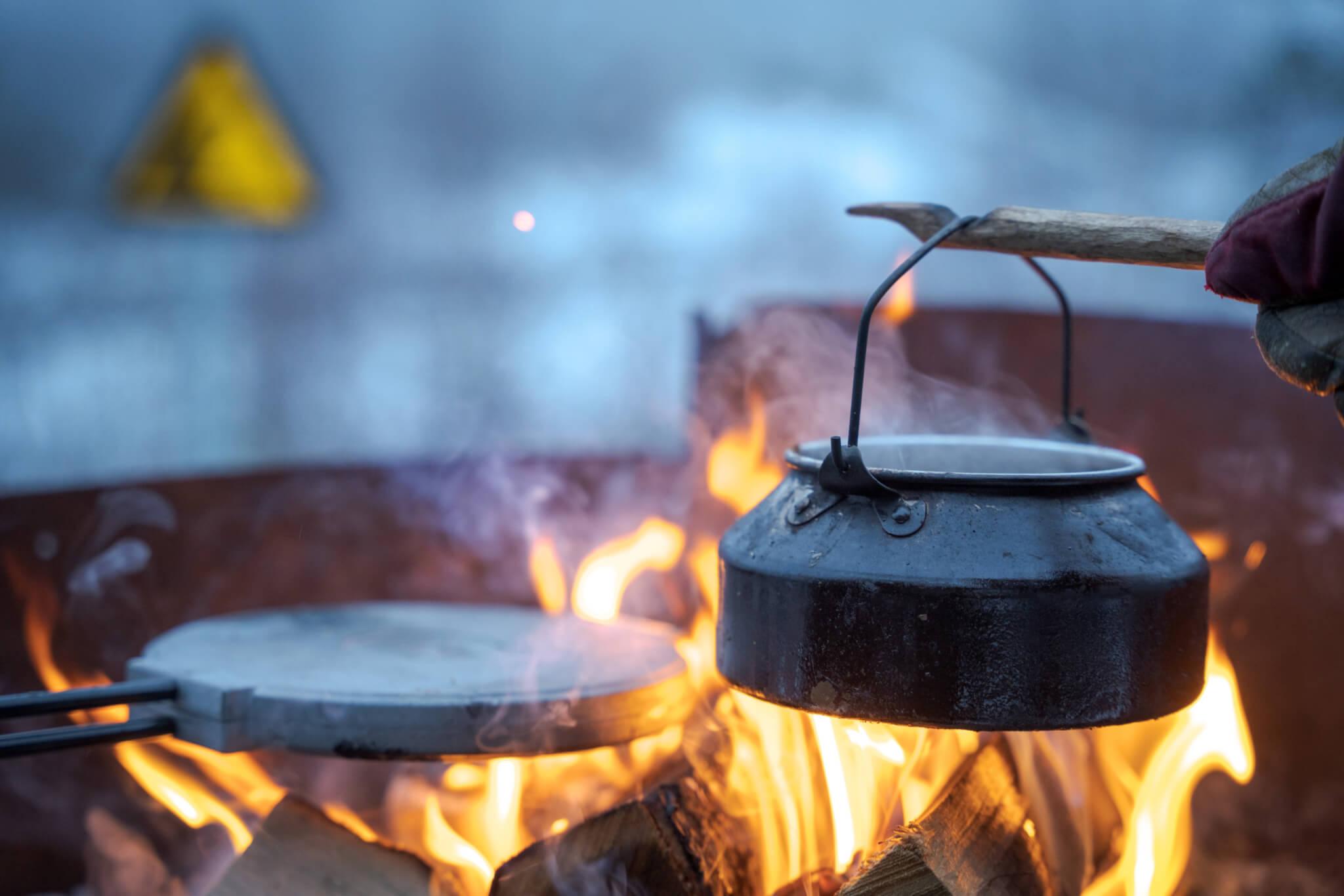 En kaffepanna över öppen eld. Tillvänster i elden syns ett våffeljärn. I bakgrunden syns en gul triangelskylt suddigt.