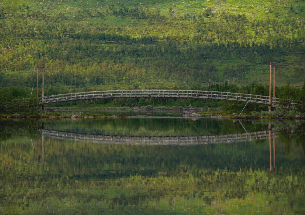 Tärnasjön. Bro över spegelblank sjö. Grön lövskog speglas i sjön.