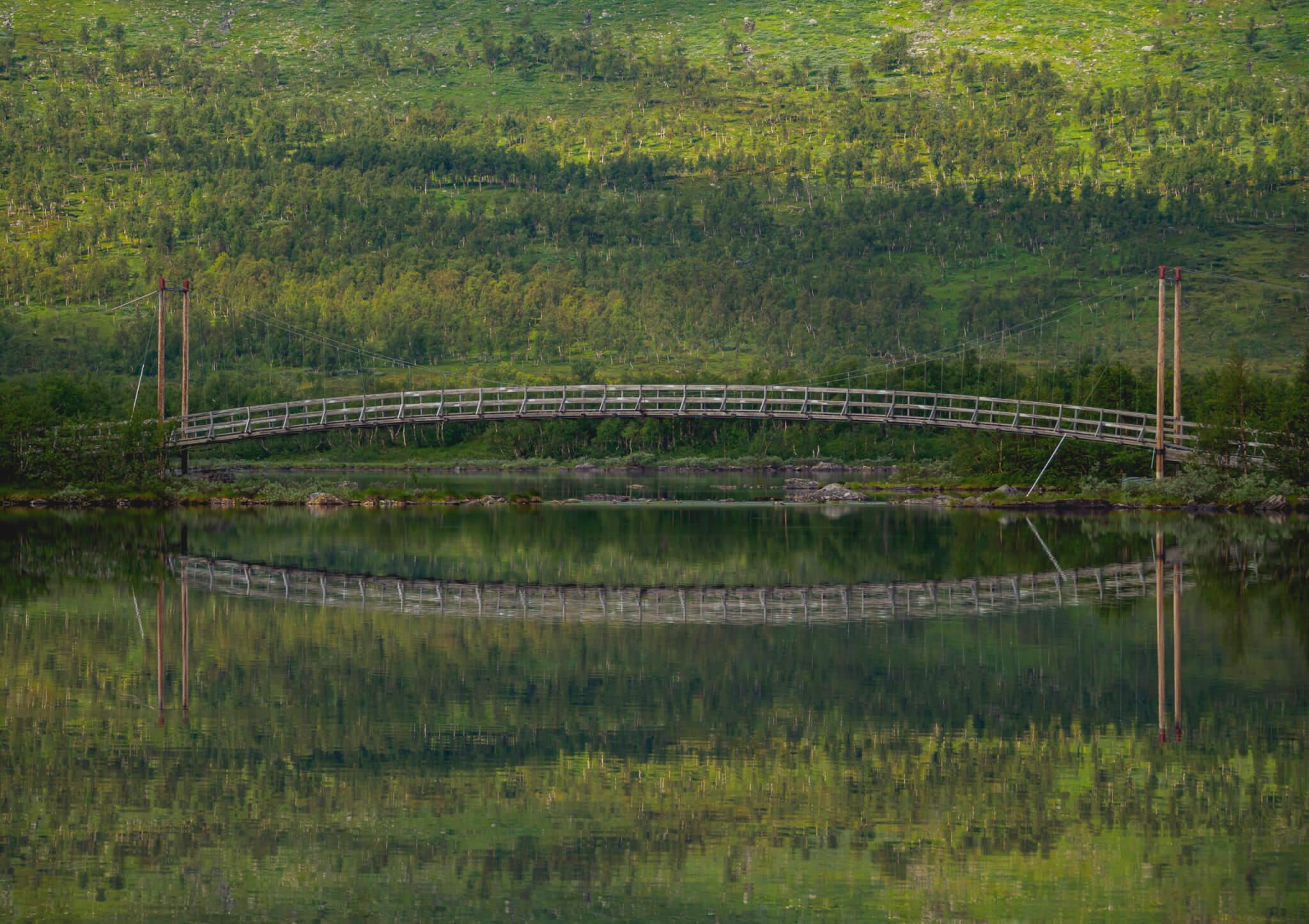 Tärnasjöbro. Bron speglas mot sjö och grön fjällbjörkskog.