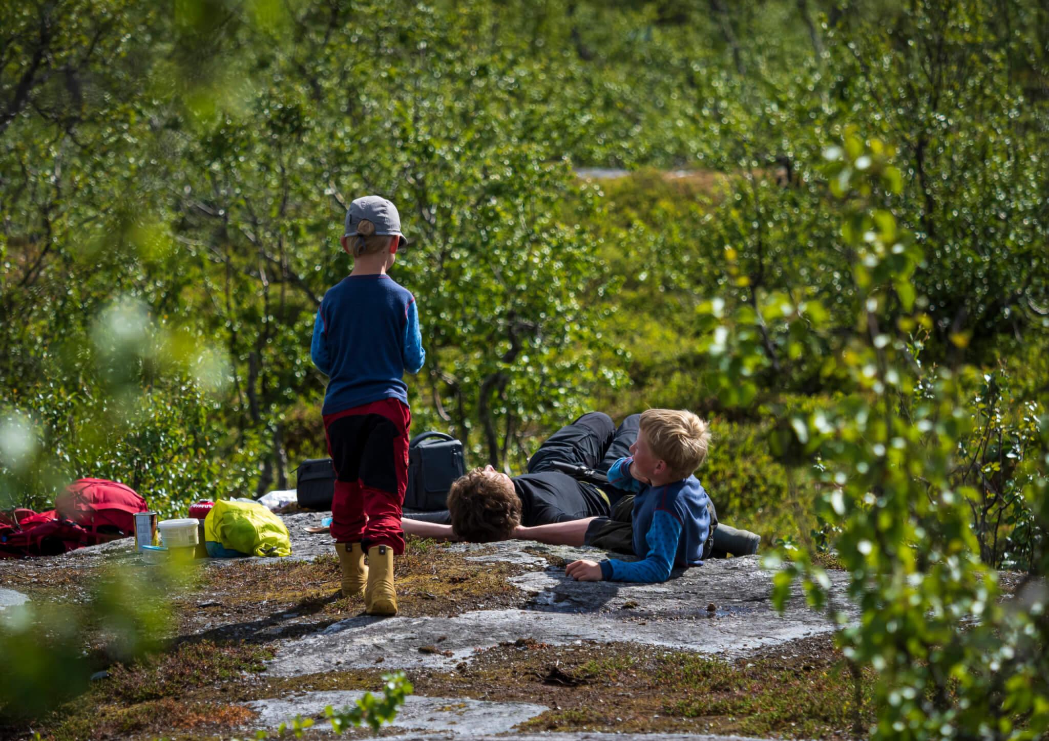 En vuxen och två barn har slagit sig ner på en stenhäll för att fika.