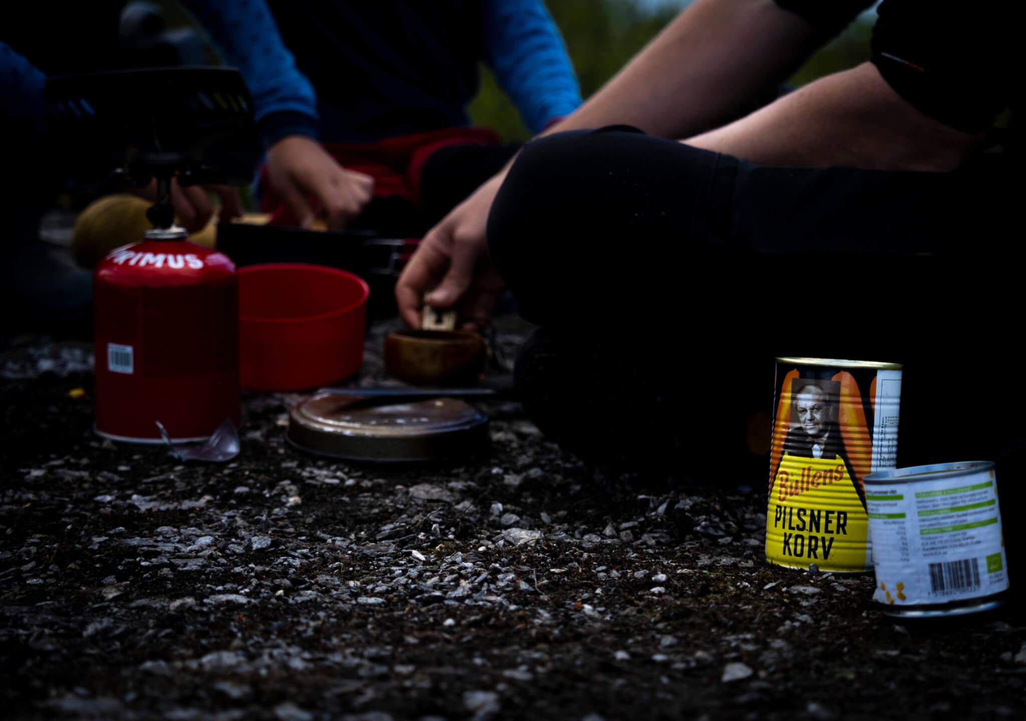 några personer sitter på marken vid ett gasolkök. En bullens pilsnerkorv-burk syns i förgrunden till höger.