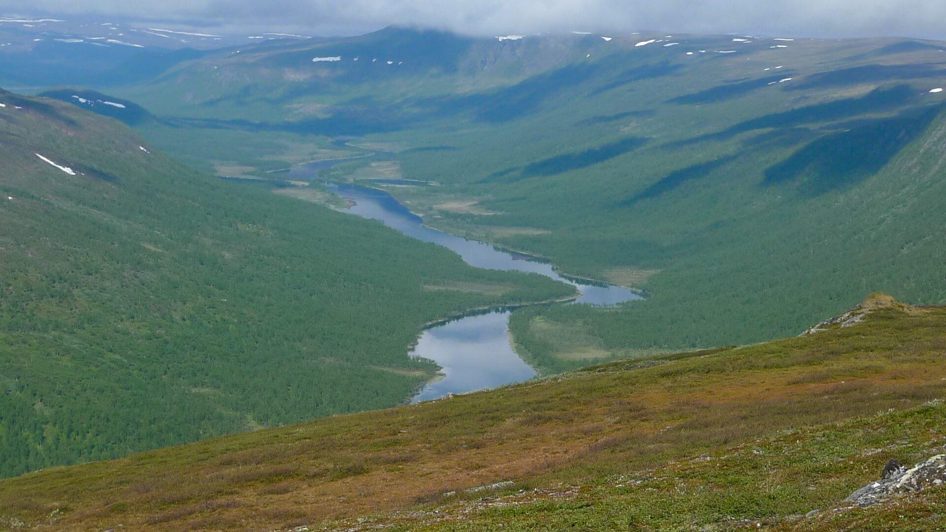 En älvdal syns från ovan. Moln skapar skuggor på vissa ställen i dalen.