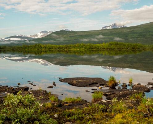 Tärnasjön ligger spegelblank en solig sommardag. Runda fjäll speglar sig i vattnet.